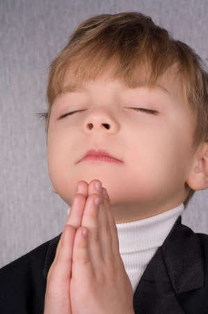 A six years boy with his hands clasped together in prayer photo