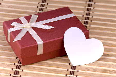 One red gift box with white ribbon and bow and heart isolated photo