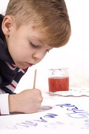Beautiful little boy is drawing with gouaches on paper photo