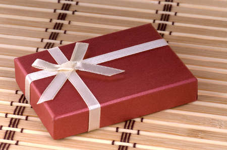 One red gift box with white ribbon and bow photo