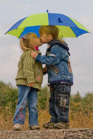 Little boy kiss girl, under umbrella in autumn day photo
