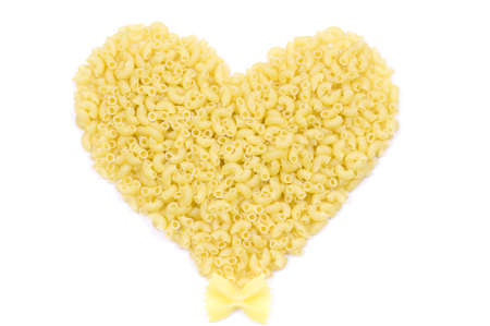 Different italian pasta in the form of heart over white. Italian food background for Valentines Day. photo