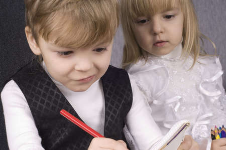 Beautiful little girl and boy is drawing with crayons on paper Stock Photo - 6534538