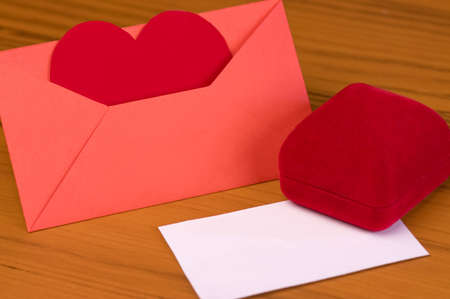 Blank Valentines Day card on table, envelope with heart and red gift box photo