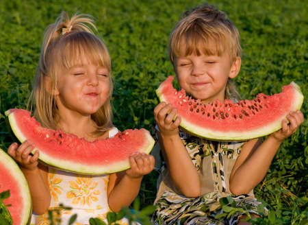 Little girl and boy with a piece of watermelon in hands photo