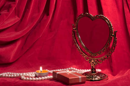 Mirror in the form of heart, pearly necklace, light,  red gift box. Valentines day card. photo