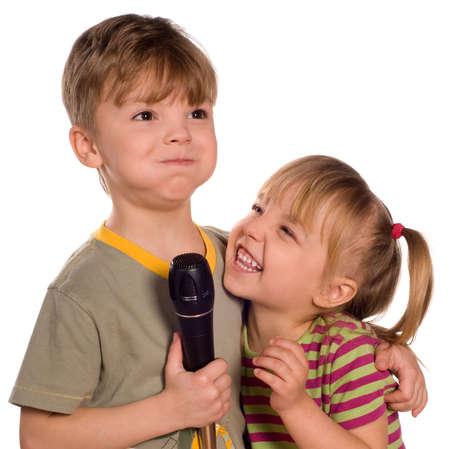 niño y niña: Niño cantando con un micrófono. Divertido poco chica y chico aislados sobre fondo blanco. Hermosa modelo caucásicos. Foto de archivo