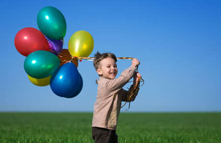 Happy child with balloons running on the spring field  photo
