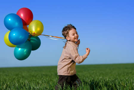 colored play: Happy child with balloons running on the spring field