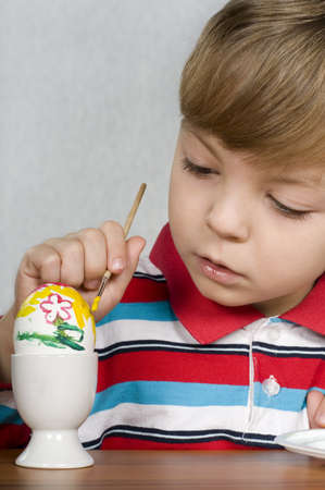 Happy little boy painting the easter eggs photo