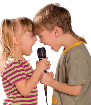 Child singing with a microphone. Funny little girl and boy isolated on white background. Beautiful caucasian model. Stock Photo - 7056805