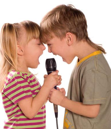 persona cantando: Ni�o cantando con un micr�fono. Divertido poco chica y chico aislados sobre fondo blanco. Hermosa modelo cauc�sicos. Foto de archivo
