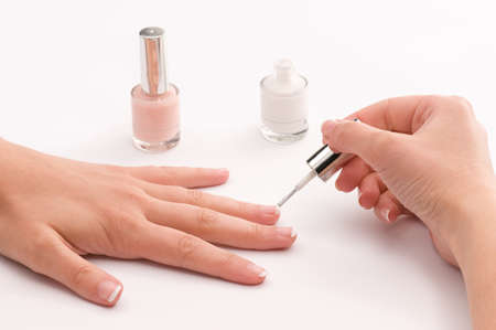 Woman covering her nails with nail polish photo