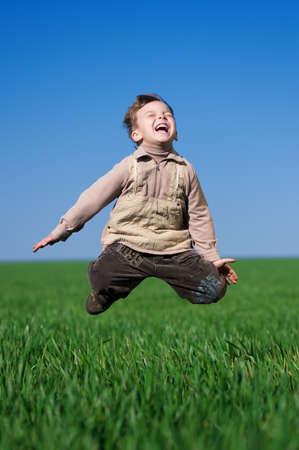 Happy little boy jumping in field against blue sky photo