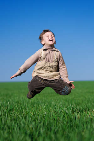 outstretch: Happy little boy jumping in field against blue sky Stock Photo