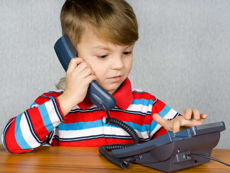 Communication - Portrait of little child in T-shirt talking to an telephone photo