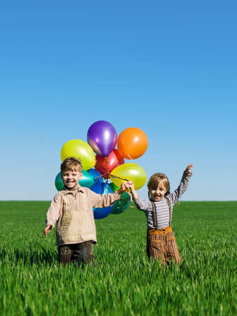 Happy sister and brother with balloons walking on the spring field