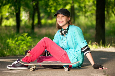 Beautiful teenage girl with skateboard in the green park Stock Photo - 7349764