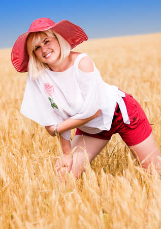 Beautiful woman with hat in wheat meadow on sunny day photo