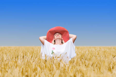 Beautiful woman with hat in wheat meadow on sunny day Stock Photo - 7349473