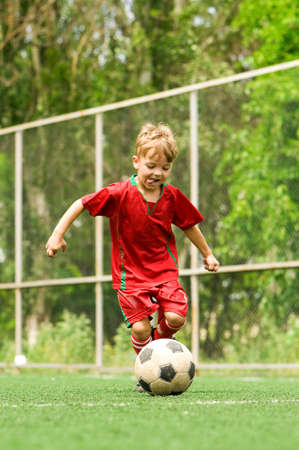 Funny young caucasian boy with soccer ball photo