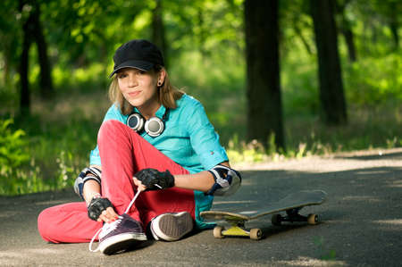 Beautiful teenage girl with skateboard in the green park Stock Photo - 7463187