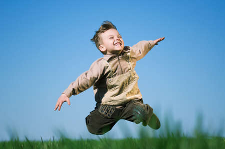 Happy little boy jumping in field against blue sky photo