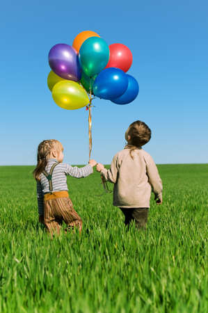 hand colored: Happy sister and brother with balloons walking on the spring field