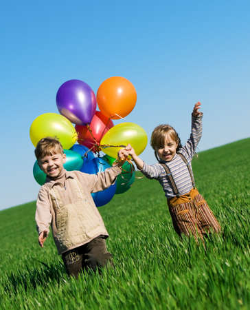 Happy sister and brother with balloons walking on the spring field Stock Photo - 7496730