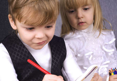 Beautiful little girl and boy is drawing with pencils on paper photo