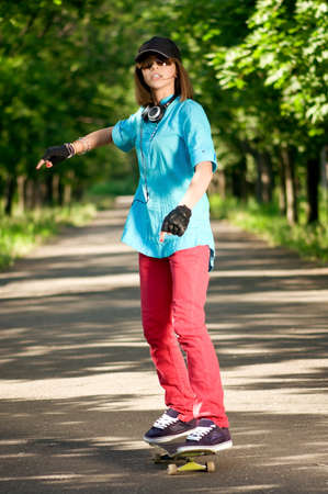 Beautiful teenage girl with skateboard in the green park Stock Photo - 7489043