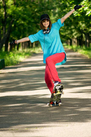 Beautiful teenage girl with skateboard in the green park Stock Photo - 7489084