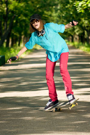 Beautiful teenage girl with skateboard in the green park Stock Photo - 7489088