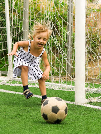 Funny young caucasian girl with soccer ball photo