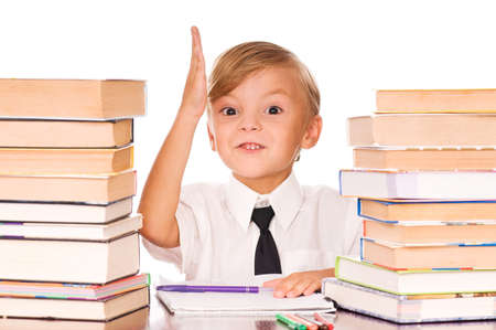Portrait of a cute little boy sitting in classroom before books. Isolated over white background. Stock Photo - 7647370