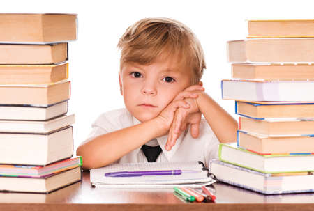 Portrait of a cute little boy sitting in library before books. Isolated over white background. Stock Photo - 7647373