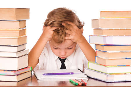 emotional stress: Portrait of a cute little boy sitting in library before books. Isolated over white background. Stock Photo