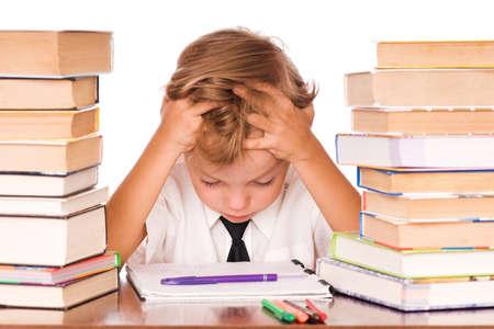inteligencia emocional: Retrato de un niño lindo, sentado en la biblioteca antes de libros. Aislados sobre fondo blanco.  Foto de archivo