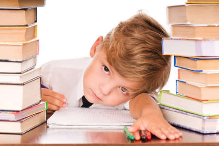 Portrait of a cute little boy sitting in library before books. Isolated over white background. Stock Photo - 7694661