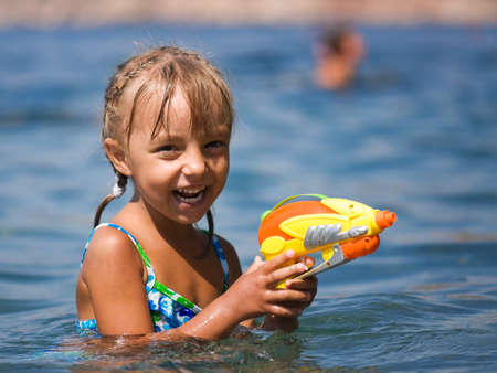 Happy little girl with water pistol has fun in the sea photo