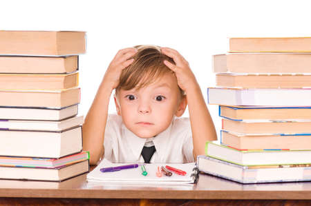 work writing: Six year old boy surrounded by piles of books isolated against a white background Stock Photo