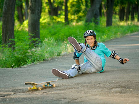 Beautiful teenage girl with skateboard in the green park photo