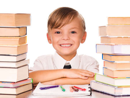 Six year old boy surrounded by piles of books isolated against a white background Stock Photo - 7790632