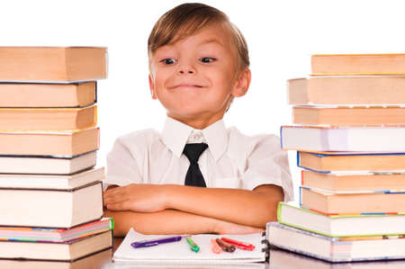 Six year old boy surrounded by piles of books isolated against a white background photo