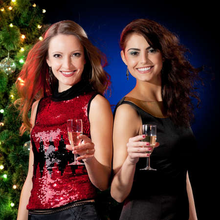 Christmas women with glasses of champagne near a Christmas tree photo