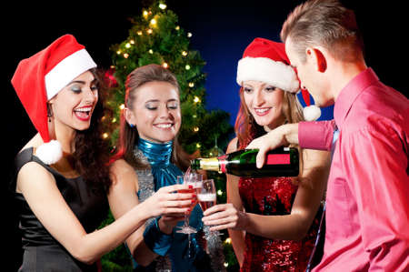 Christmas women and man with glass of champagne near a Christmas tree photo