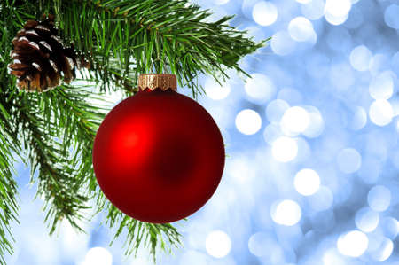 Red bauble on artificial christmas firtree on abstract blue background Stock Photo - 8280620