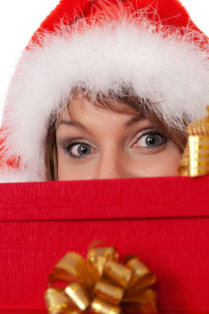 Christmas girl holding gifts wearing Santa hat. Close-up. Stock Photo - 8280615