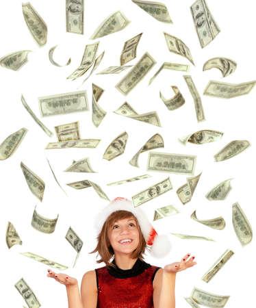 �cash: Smiling christmas girl catching falling dollars banknotes wearing Santa hat. Isolated on white background. Stock Photo