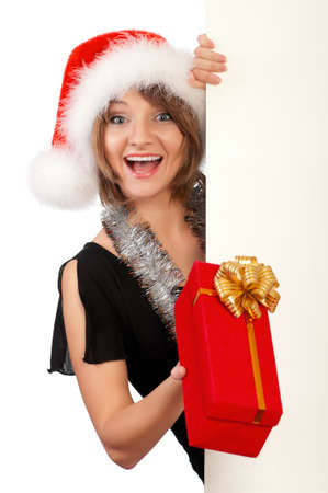 Smiling christmas girl holding gift box wearing Santa hat. Isolated on white background. Stock Photo - 8280624